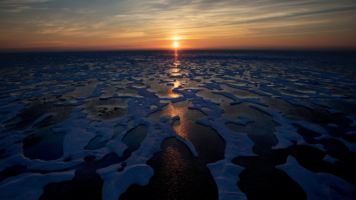 The midnight sun shines across sea ice along the Northwest Passage in the Canadian Arctic...