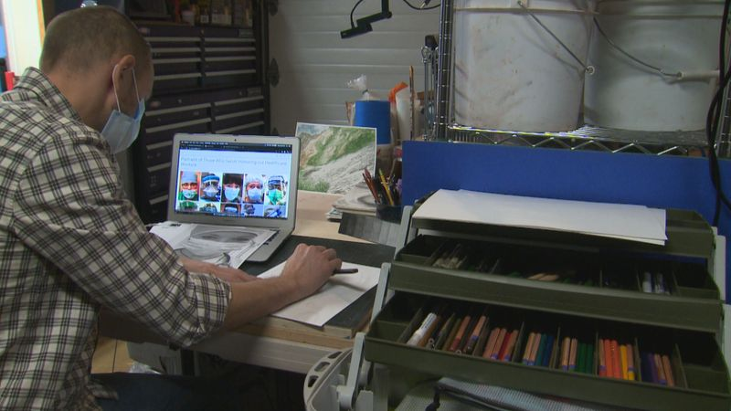 Jacob Bera, an art teacher at Eagle River High School, scrolls through images submitted as part...