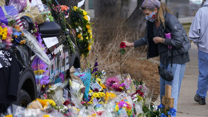 A mourner places a rose amid bouquets in tribute around a police cruiser for Boulder, Colo.,...