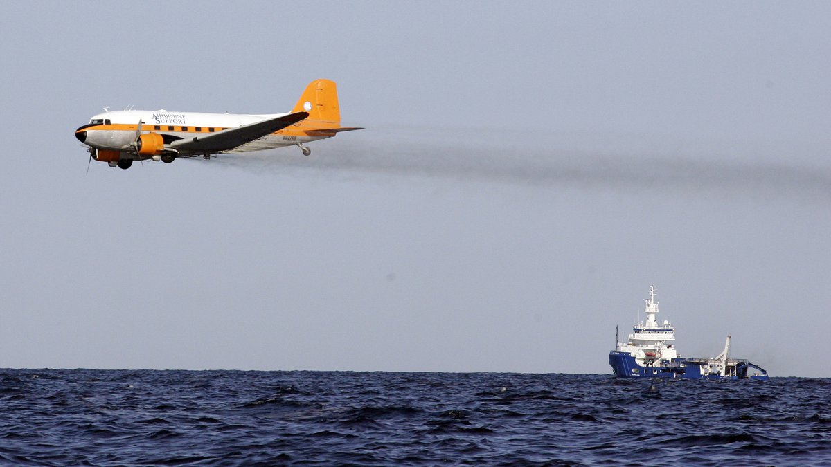 In this April 27, 2010 file photo, a dispersant plane passes over an oil skimmer as it cleans...