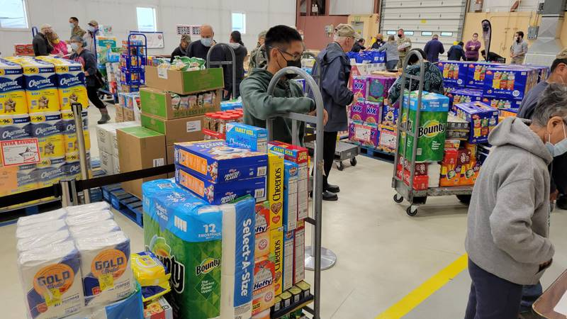 People line up to pay for items at commissary set up at AKNG hangar in Bethel