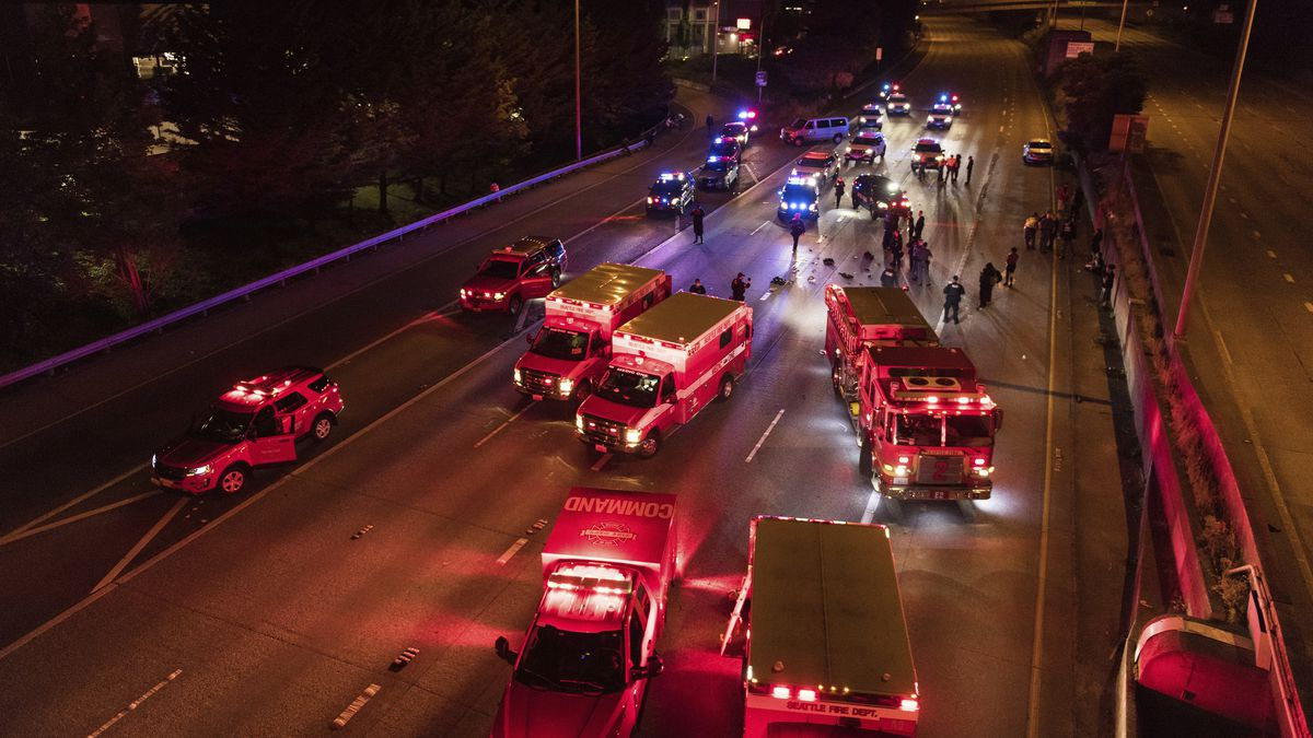 Emergency personnel work at the site where a driver sped through a protest-related closure on the Interstate 5 freeway in Seattle, authorities said early Saturday, July 4, 2020.(James Anderson via AP)