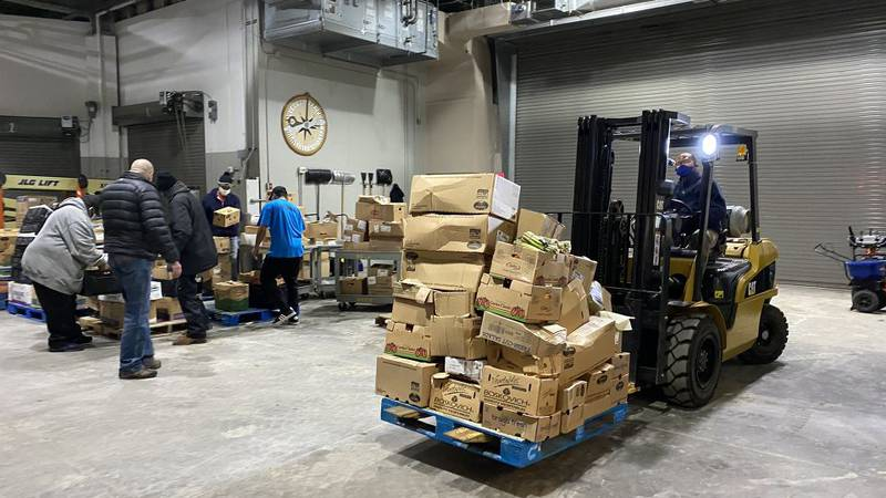 People unload thousands of pounds of food for Bean's Cafe on Christmas Eve.