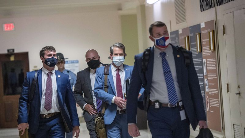 Georgia Gov. Brian Kemp, second from right, leaves the Georgia State Capitol Building after he...