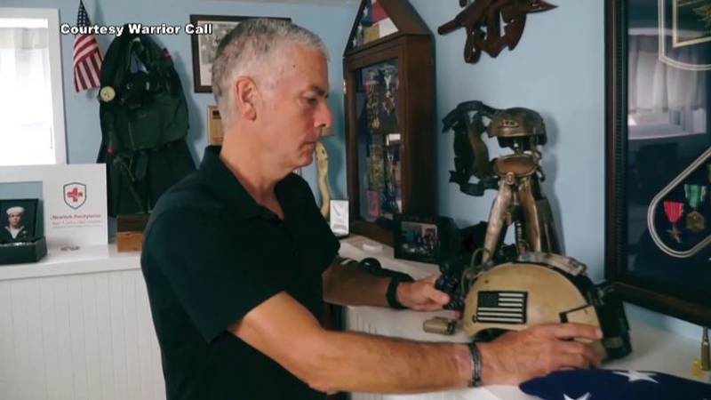 Retired Navy SEAL Frank Larkins looks at tribute to his son, also a SEAL, who died by suicide...