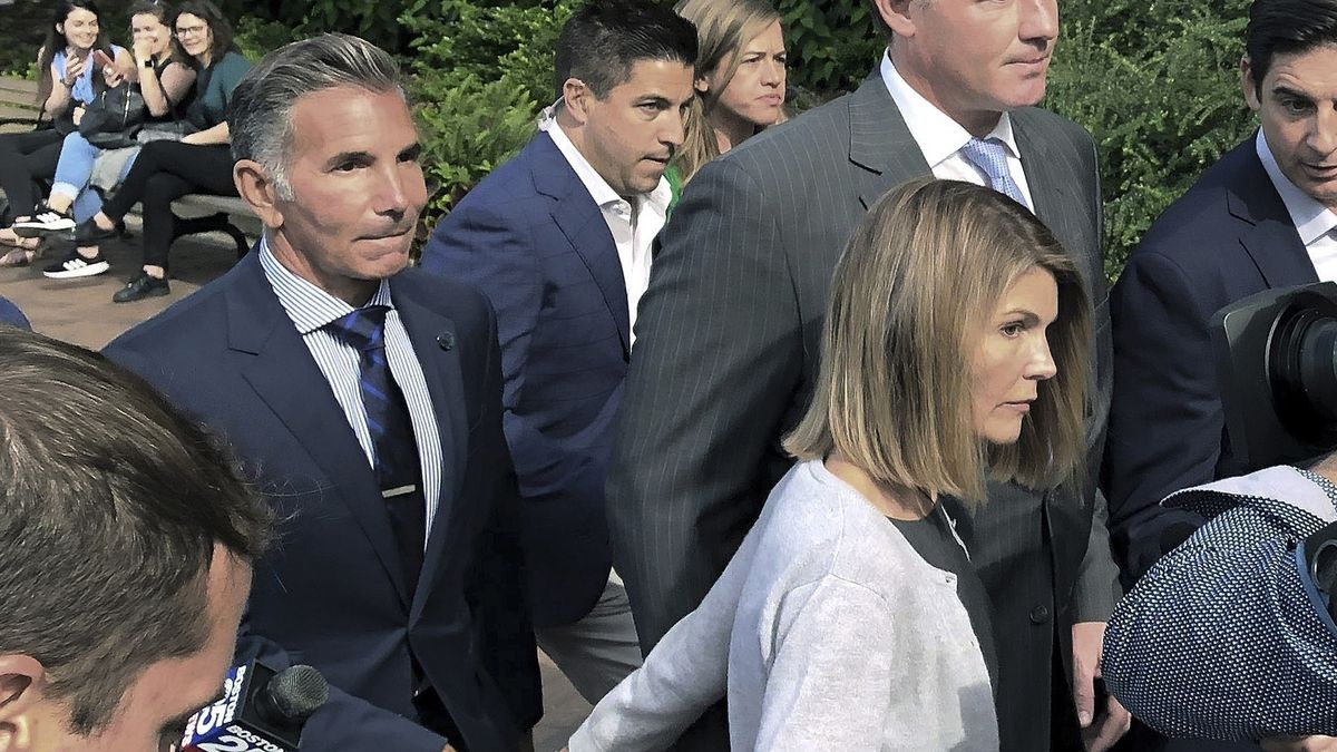 Lori Loughlin departs federal court in Boston with her husband, Mossimo Giannulli, left, after...