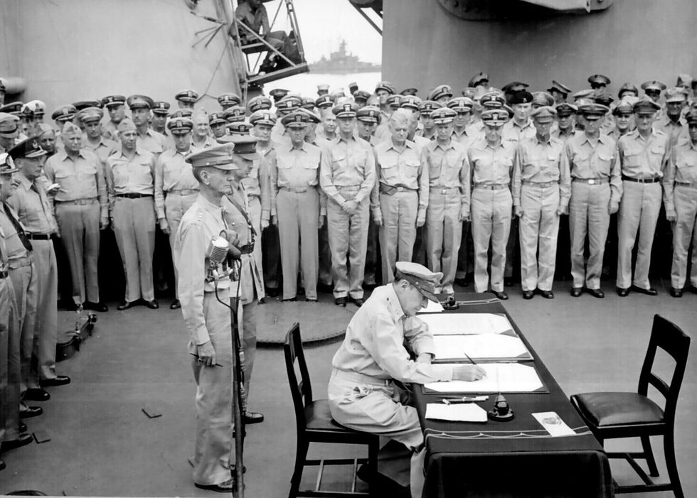 General of the Army Douglas MacArthur sign documents during the surrender ceremony aboard...