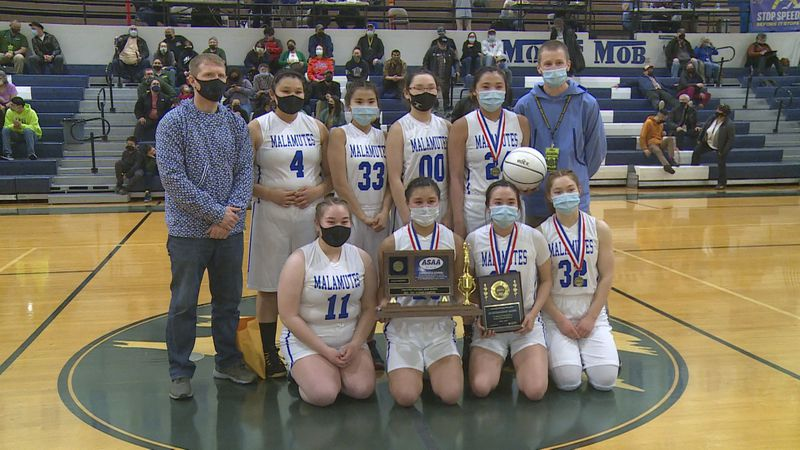 The Newhalen girls basketball team takes a picture with the trophy after winning the 2021 state...