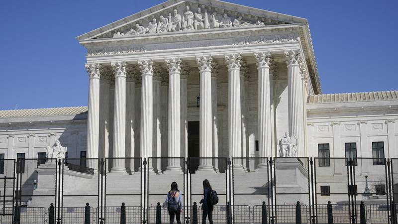 FILE - In this March 21, 2021 file photo, people view the Supreme Court building from behind...