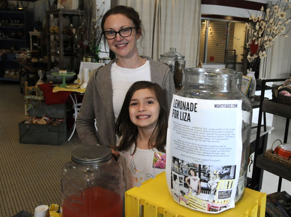Elizabeth Scott and her 7-year-old daughter Liza Scott, who is running a lemonade stand to help...