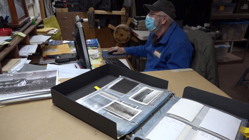 Richard Estelle preserving old photos at his computer at the Palmer Museum of History and Art...