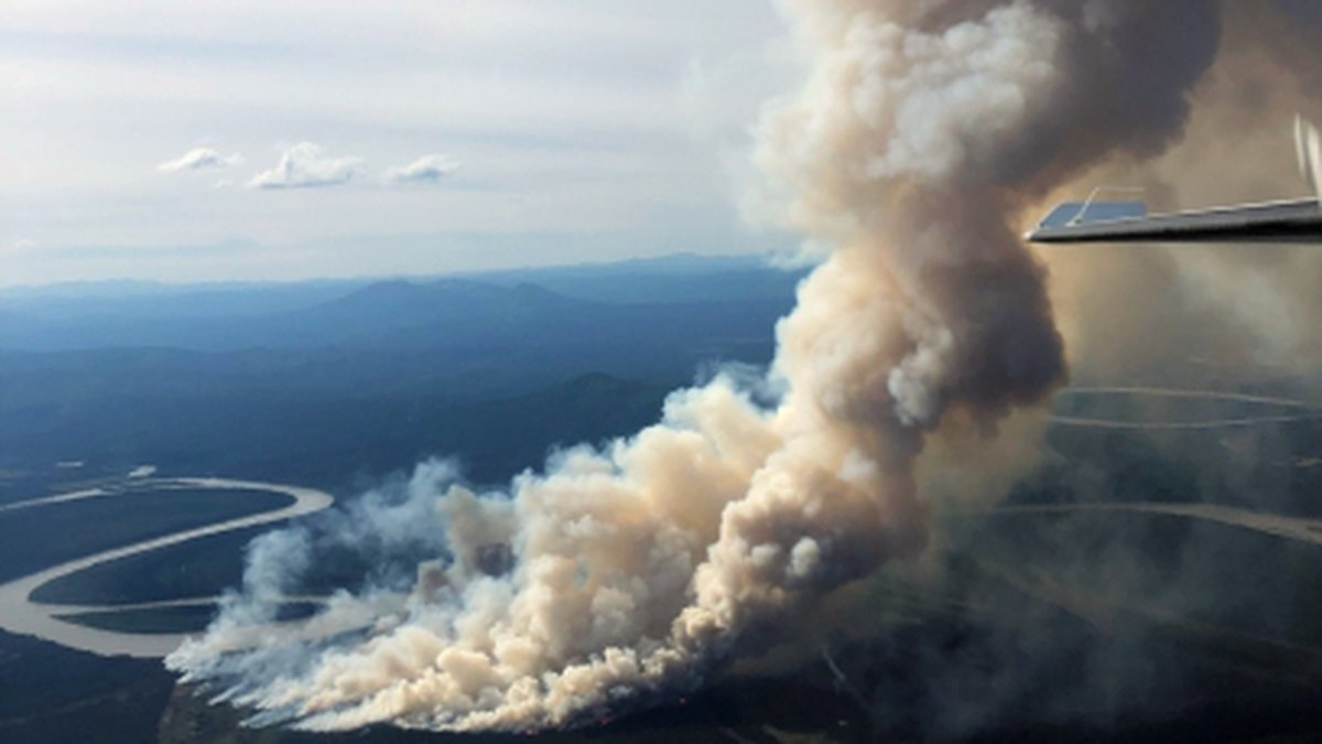 The About Mountain fire burns near the Kuskokwim River about 6 miles from McGrath, Alaska on...