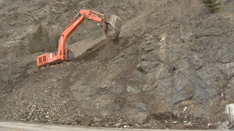 An excavator is clawing at the cliffs along the Seward Highway