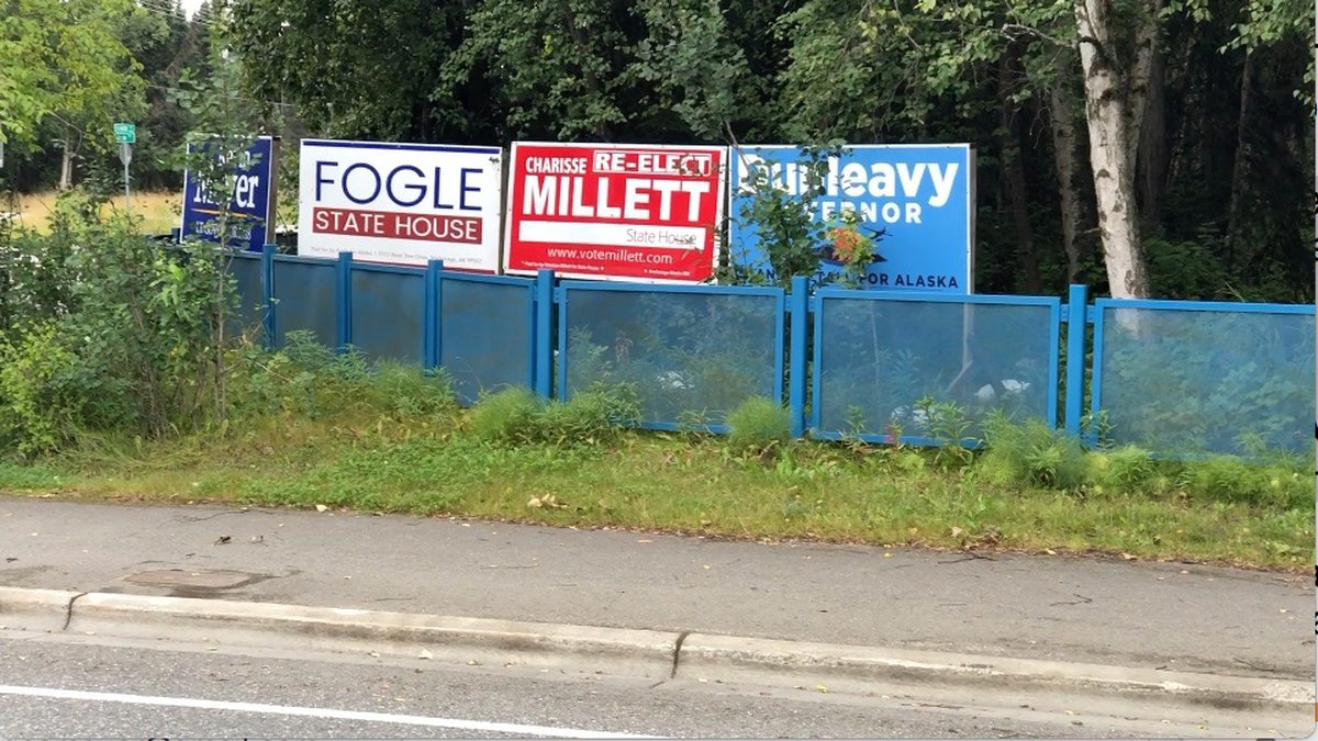 Campaign signs behind a fence by a state road intersection are the focus of a civil liberties...