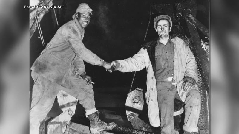 A historic handshake between a Black and white soldier commemorates the completion of the...