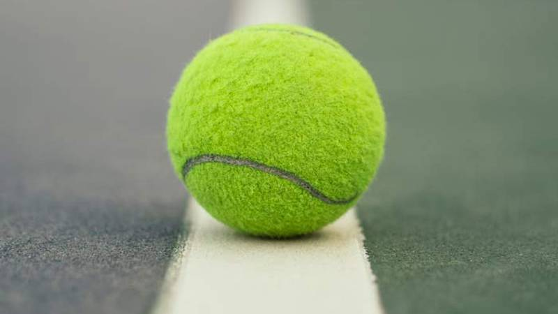 A tennis ball sits on a court.
