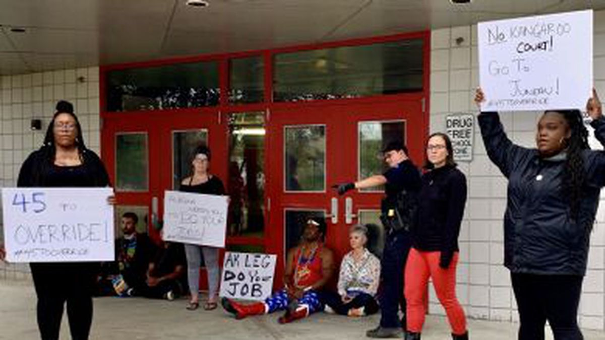 Protestors greeted lawmakers at Wasilla Middle School Wednesday morning, the same day a vote was scheduled in Juneau to override Gov. Mike Dunleavy's vetoes of the budget. (Courtesy Adam Greenberg)