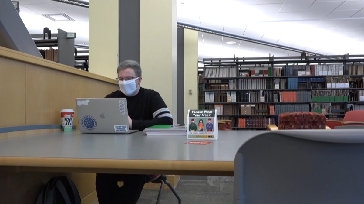 A student wearing a mask works on his laptop at the Consortium Library on the University of...