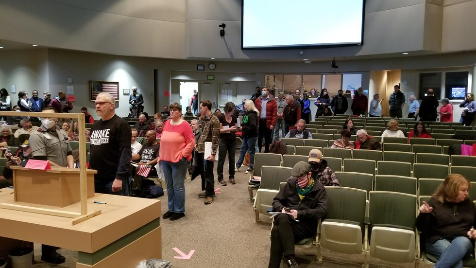 Residents line up to testify on a proposed ordinance that would require masks in the...