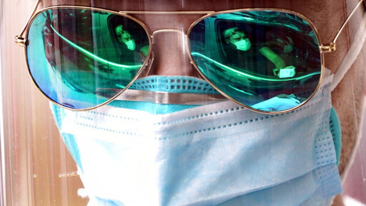 A patient is reflected in the sunglasses of medical student Bryan Delgado as he gathers his...