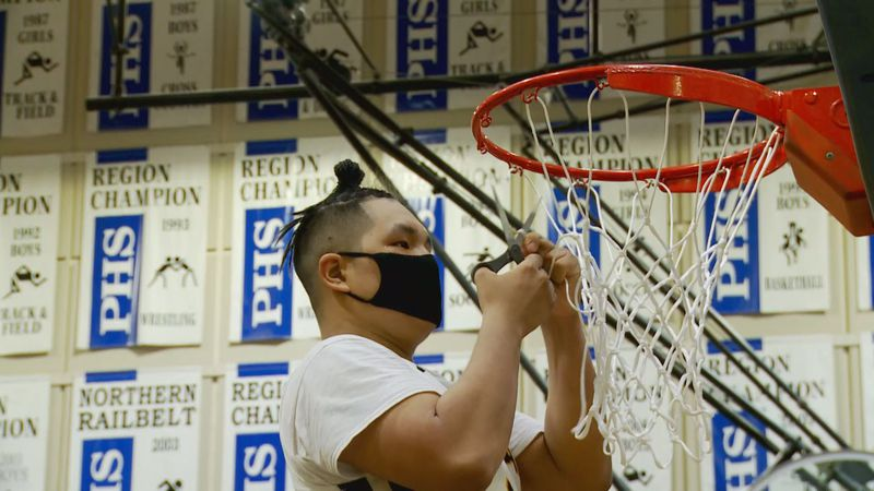 The Tikigaq boys basketball team cuts down the nets after winning the 2021 state championship