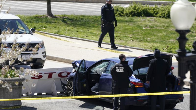U.S. Capitol Police officers stand near a car that crashed into a barrier on Capitol Hill in...