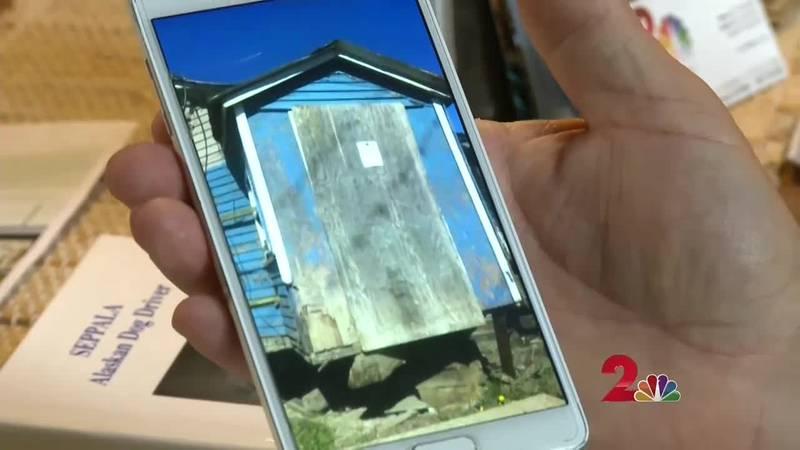 A member of the Leonhard Seppala House Project shows a photo of the Seppala House. (KTUU)