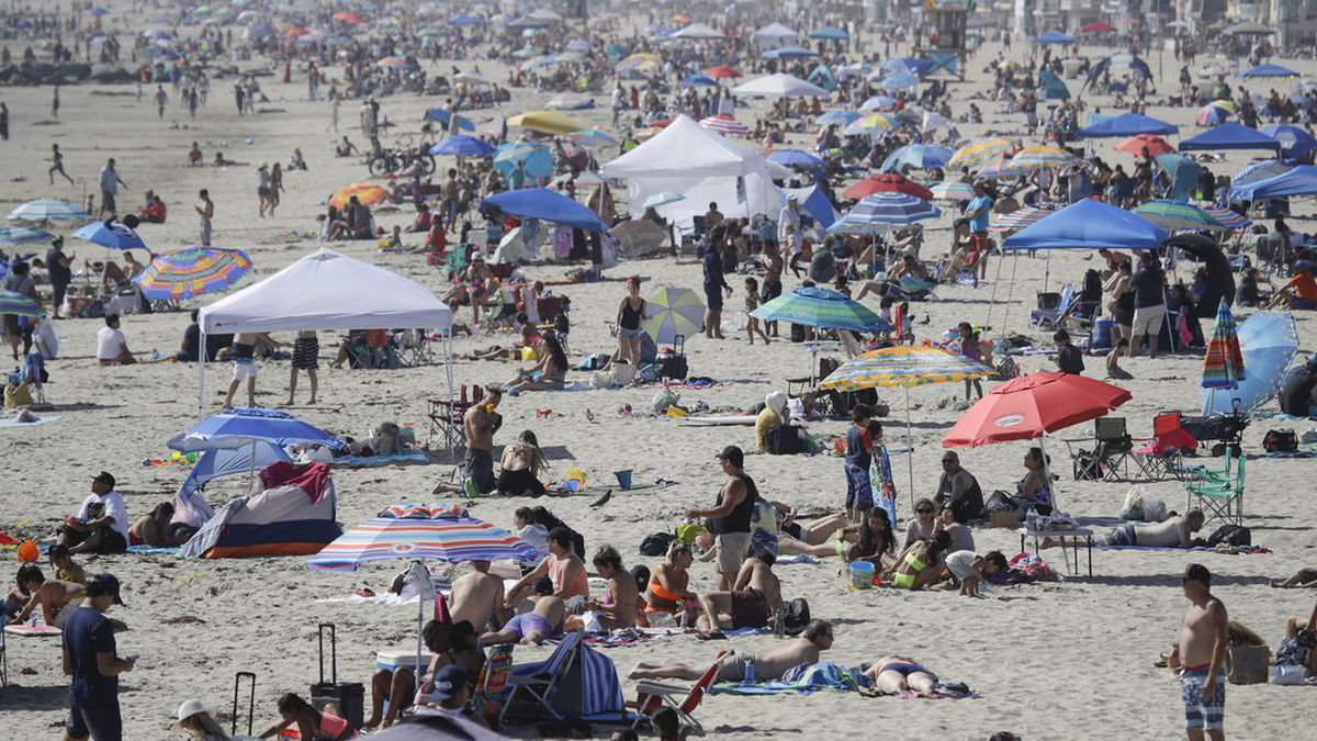 FILE - In this May 24, 2020, file photo, visitors gather on the beach during the Memorial Day weekend in Newport Beach, Calif. California's mood has gone from optimistic to sour as coronavirus cases and hospitalizations are on the rise heading into the July 4th weekend. Gov. Gavin Newsom has ordered bars and indoor restaurant dining closed in most of the state, many beaches are off limits, and he's imploring Californians to avoid holiday gatherings with family and friends. (Source: AP Photo/Marcio Jose Sanchez, File/AP)