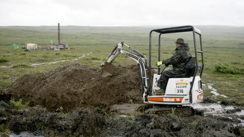 In this July 13, 2007, Associated Press file photo, a worker with the Pebble Mine project digs...