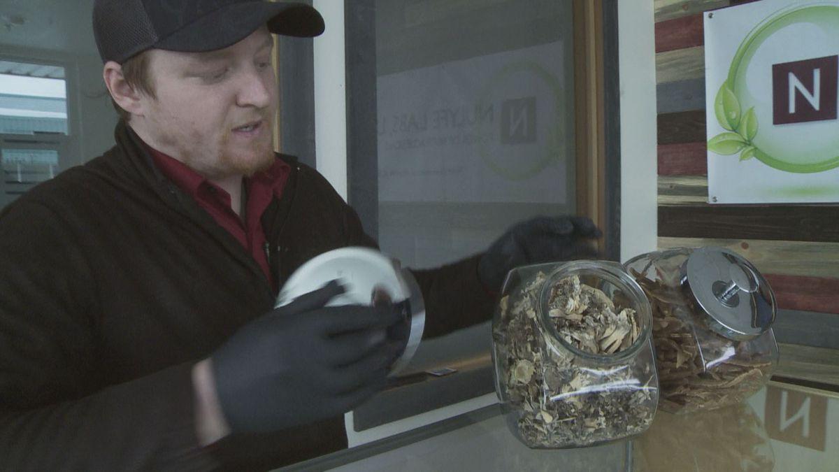 Anthany Dellapietro opens a jar of shitake mushrooms, a product he sells at his Wasilla...