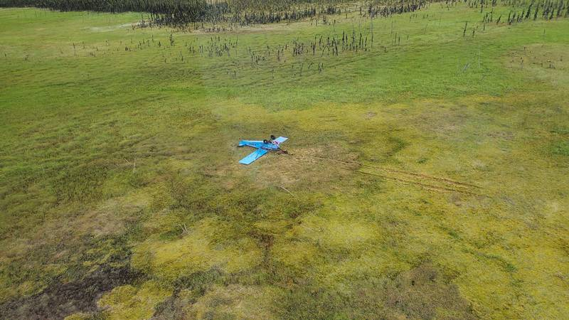 An overturned Piper J3C-65 rests on an open field near Rabbit Foot Lake in the Kenai National...