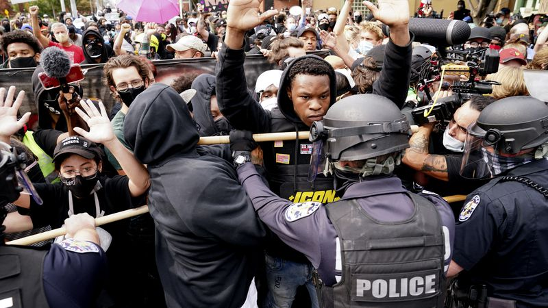 Police and protesters converge during a demonstration, Wednesday, Sept. 23, 2020, in...
