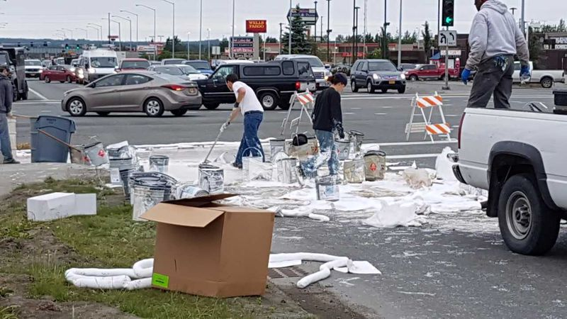 Workers rush to clean the large paint spill at the Dimond and Old Seward intersection. Photo...