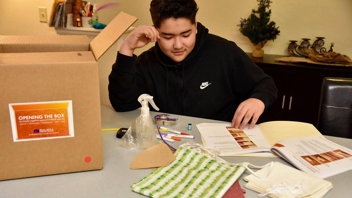 Eighth-grade student Blaise Trombetti from Dzantik'i Heeni Middle School examines his kit....