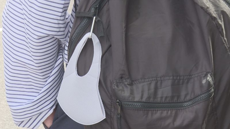 Student carries mask on backpack