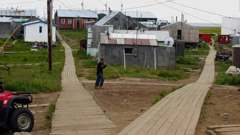 A resident of Hooper Bay, Alaska, walks to the boardwalk in the village in this July 11, 2003,...