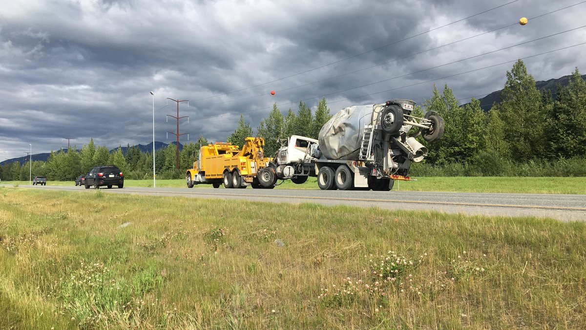 A concrete truck is towed from where it rolled into a median on the Glenn Highway Thursday....