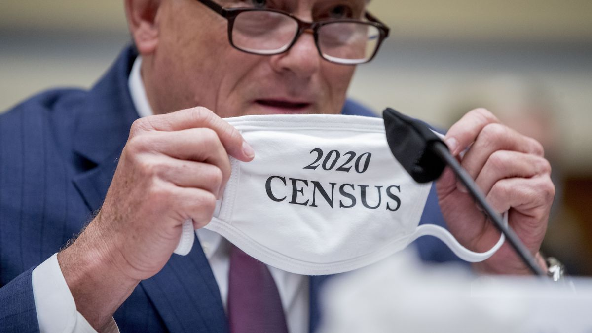 """Census Bureau Director Steven Dillingham holds up his mask with the words """"2020 Census"""" as he..."""